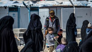 A member of Kurdish internal security stands guard as Women lead children ahead of departure during the release of another group of Syrian families from the Kurdish-run al-Hol camp which holds suspected relatives of Islamic State (IS) group fighters, in Hasakeh governorate in northeastern Syria, on January 28, 2021.