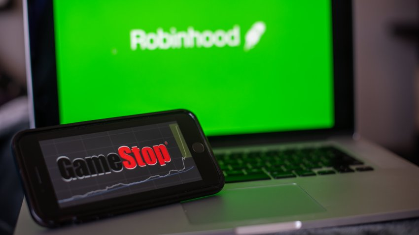 The GameStop Corp. logo on a smartphone and the Robinhood website on a laptop