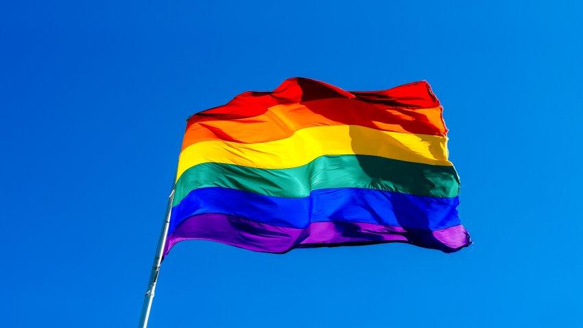 Rainbow flag waving in the wind against a clear blue sky