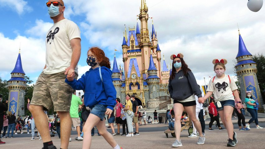 A masked family walks past Cinderella Castle in the Magic Kingdom in DisneyWorld