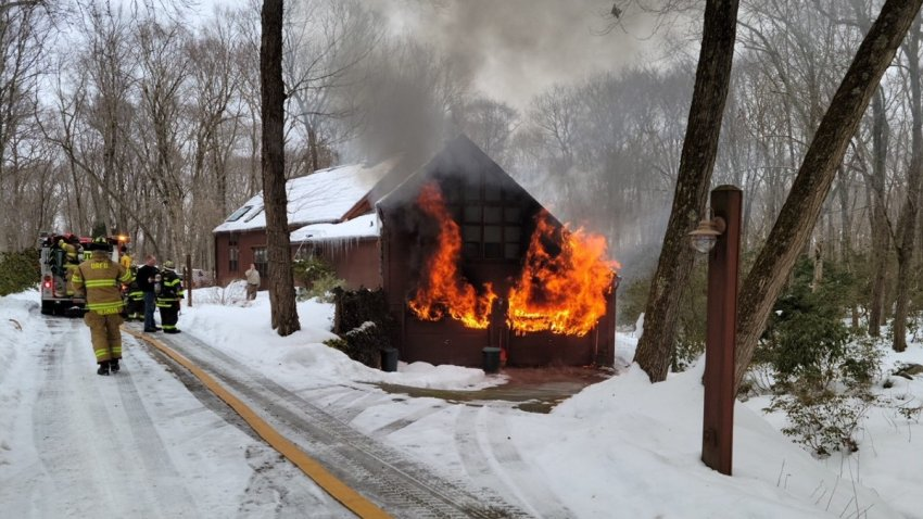 flames shoot from the garage of a home in Deep River