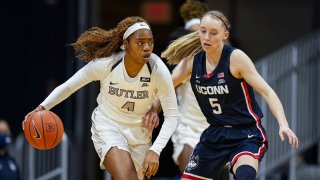 Butler guard Okako Adika (4) drives on Connecticut guard Paige Bueckers (5) during the first quarter of an NCAA college basketball game in Indianapolis, Saturday, Feb. 27, 2021.