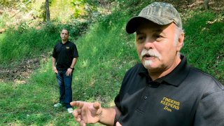 FILE-This Sept. 20, 2018 file photo, Dennis Parada, right, and his son Kem Parada stand at the site of the FBI's dig for Civil War-era gold in Dents Run, Pennsylvania. Government emails released under court order show that FBI agents were looking for gold when they excavated Dent's Run in 2018, though the FBI says that nothing was found.