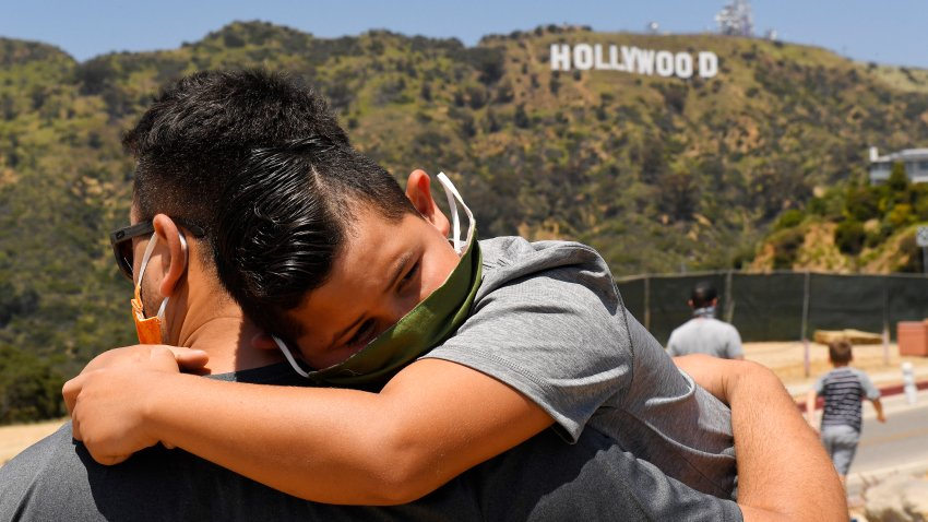 a father holds his son near the famed Hollywood sign during the coronavirus outbreak in Los Angeles