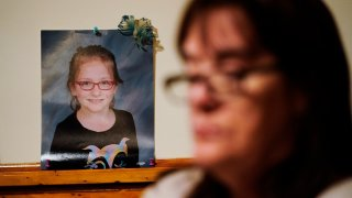 Patti Burt poses for a portrait near a photo of her granddaughter, 9-year-old Ava Lerario,