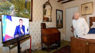 Renee Bodin, 94 years old, watches French President Emmanuel Macron's televised speech in her bedroom in Happonvilliers, near Chartres, eastern France, on March 31, 2021.