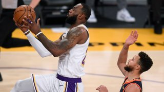 LOS ANGELES, CALIFORNIA - FEBRUARY 28: LeBron James #23 of the Los Angeles Lakers scores on a layup past Stephen Curry #30 of the Golden State Warriors during the second quarter at Staples Center on February 28, 2021 in Los Angeles, California.