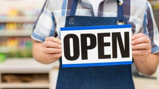 File image of a grocery store worker holding an 'open' sign.