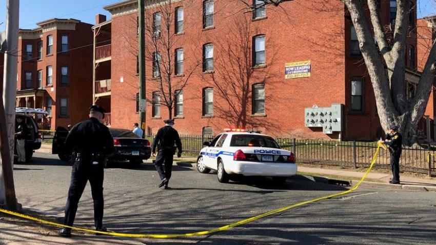 Police tape blocks off a crime scene. A police cruiser and brick building are scene in the background.