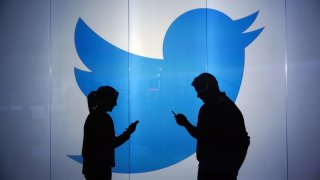 People are seen as silhouettes against an illuminated wall bearing Twitter logo