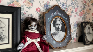 A doll sits in front of photos of Lizzie Borden in her former home.