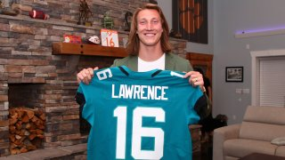 Clemson quarterback Trevor Lawrence holds up a jersey after being selected by the Jacksonville Jaguars with the first pick in the NFL football draft, Thursday, April 29, 2021, in Seneca, South Carolina.
