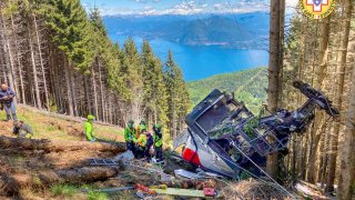 In this May 23, 2021, file photo, rescuers work by the wreckage of a cable car after it collapsed near the summit of the Stresa-Mottarone line in the Piedmont region, northern Italy. A mountaintop cable car plunged to the ground in northern Italy on Sunday, killing 14 people.