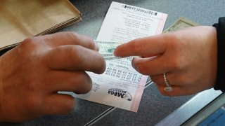 A customer purchases a Mega Millions lottery ticket at a 7-Eleven store