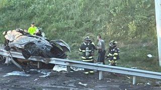 a burned and heavily damaged car resting on a guardrail after a crash in Rocky Hill