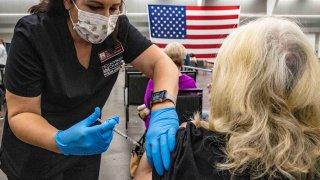 A woman gives a senior citizen a coronavirus disease (COVID-19) vaccine.