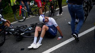 Britain's Chris Froome lays on the road after crashing during the first stage of the Tour de France cycling race