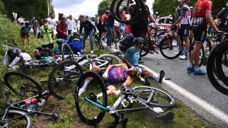 Italy's Kristian Sbaragli, left, and France's Bryan Coquard, right, lie on the ground after crashing during the first stage of the Tour de France