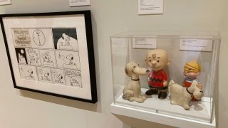 A new exhibit on dogs in cartoons and comic strips includes vinyl toys of Charlie Brown and Snoopy and Dennis the Menace and Ruff, from the private collection of exhibit curator Brian Walker