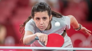 Twelve year old Hend Zaza of Syria, the youngest competitor in the Olympic Games in Tokyo, plays against Jia Liu of Austria in the Women's Singles Preliminary Round at the Tokyo Olympic Games, July 24, 2021.