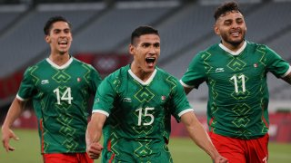 Mexico forward Uriel Antuna (center) celebrates with forward Alexis Vega (right) and midfielder Erick Aguirre after scoring the third goal during the Tokyo 2020 Olympic Games men's group A first round football match between Mexico and France at Tokyo Stadium.