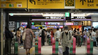 Passengers pass through the gates of a subway station in Tokyo