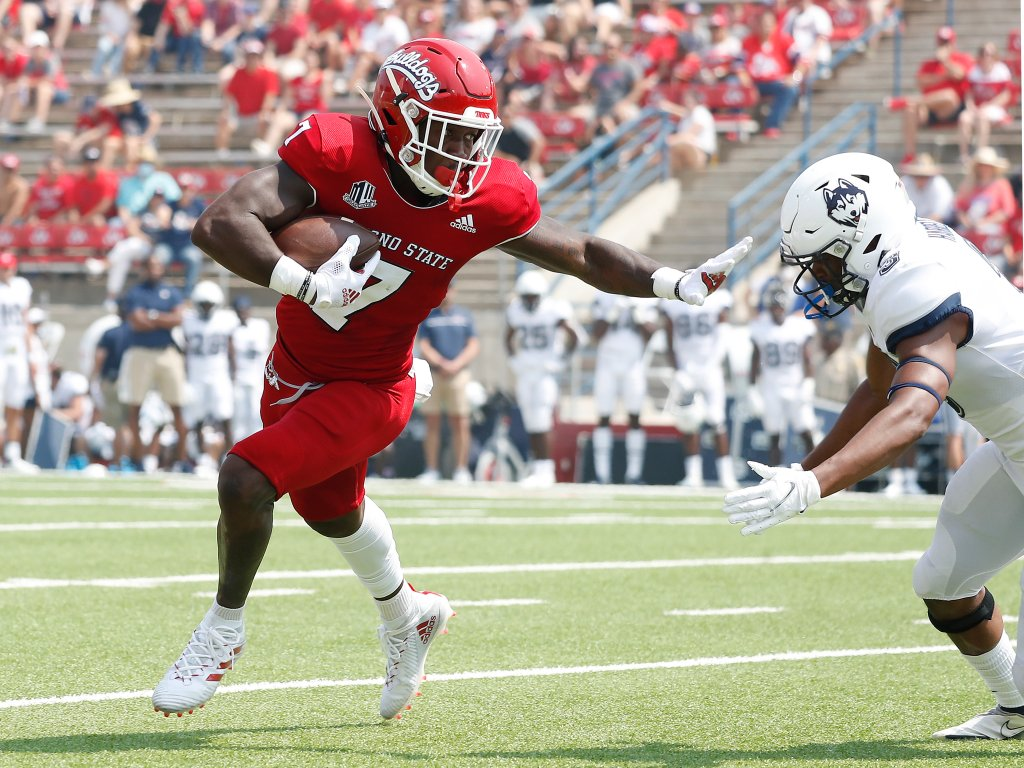 Fresno State running back Jordan Mims, left, stiff-arms a Connecticut defender during the first half of an NCAA college football game in Fresno, Calif., Saturday, Aug. 28, 2021.