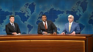 Colin Jost, Michael Che and Beck Bennett sit at anchor desk during the Weekend Update segment on Saturday Night Live.