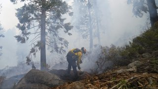 Will Fitch, fire captain from Cosumnes Fire Department, holds a fire line to keep the Caldor Fire from spreading in South Lake Tahoe, Calif., Friday, Sept. 3, 2021.
