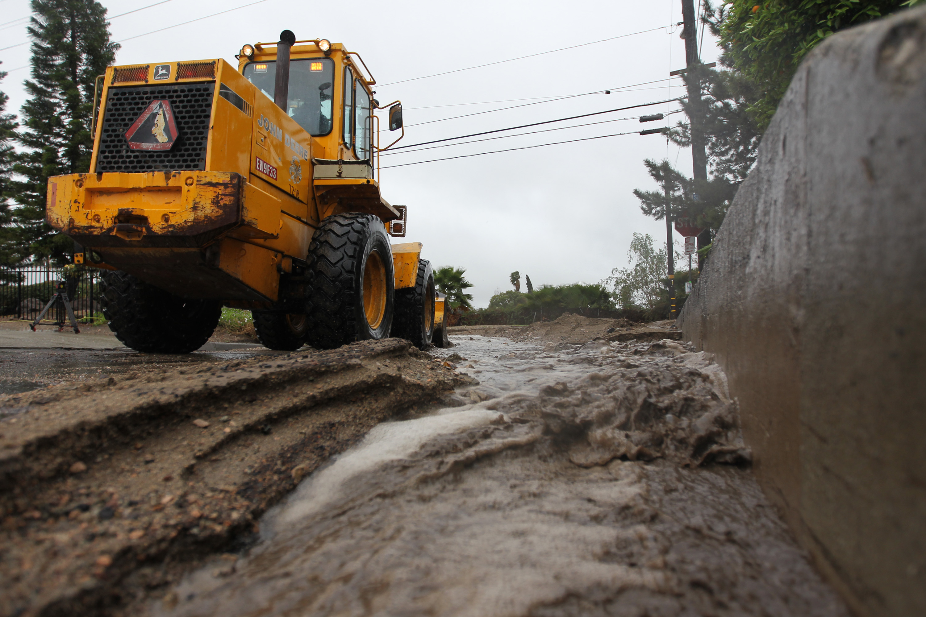 Workers clear ash, rocks and mud that have flowed onto a street below the Colby Fire burn area as a storm brings rain in the midst of record drought on February 28, 2014 in Glendora, California.