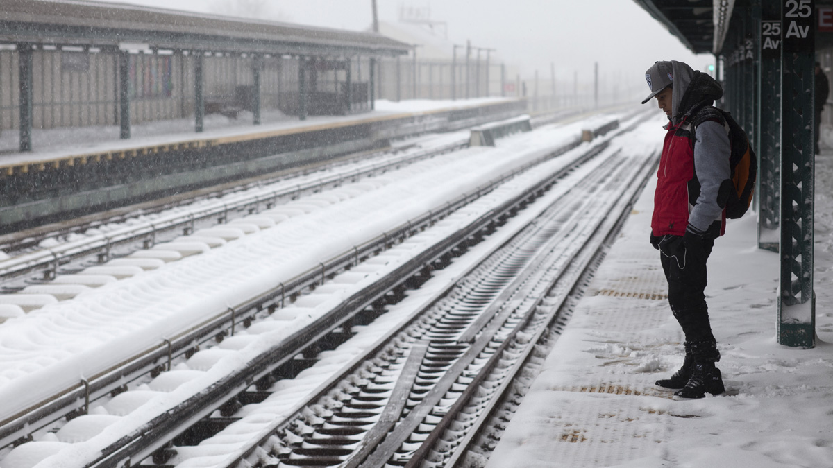 A man waits for a D train at the snow-covered 25th Avenue stop in the Brooklyn borough of New York on Saturday, Jan. 23, 2016, in New York. Service at above-ground stations was suspended later in the day due to a blizzard.