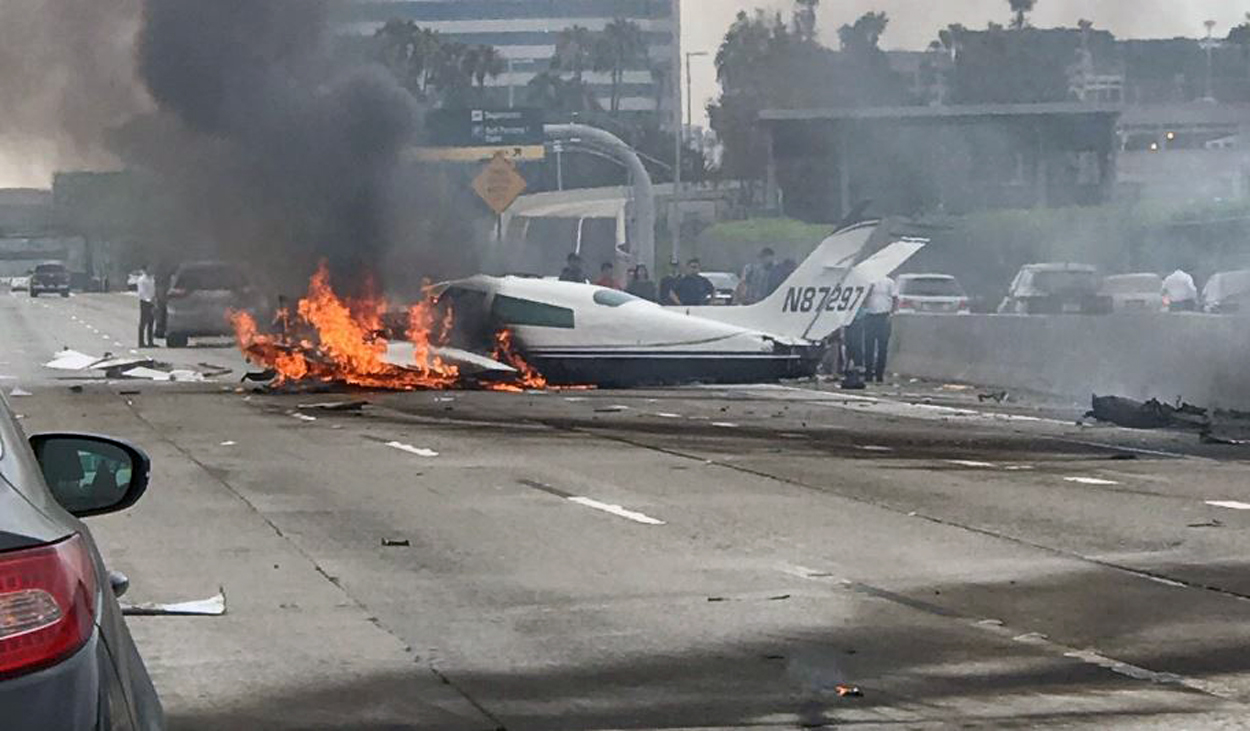 Fire burst from the belly of a plane that crashed Friday June 30, 2017 on the 405 Freeway in Santa Ana.