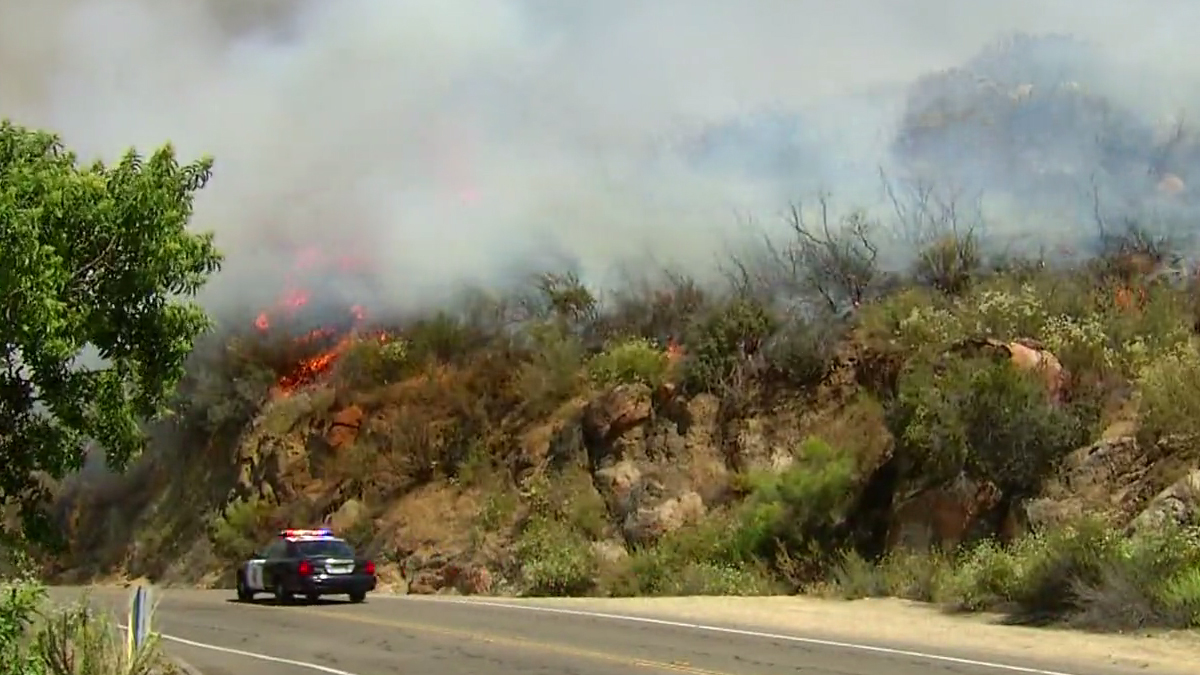A police car drives along an East County road, close to flames from the Border Fire.