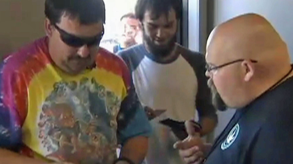 Mike Boyer, the man at left in the tie dye shirt, lost his job after turning up on the news at a marijuana store in Washington.