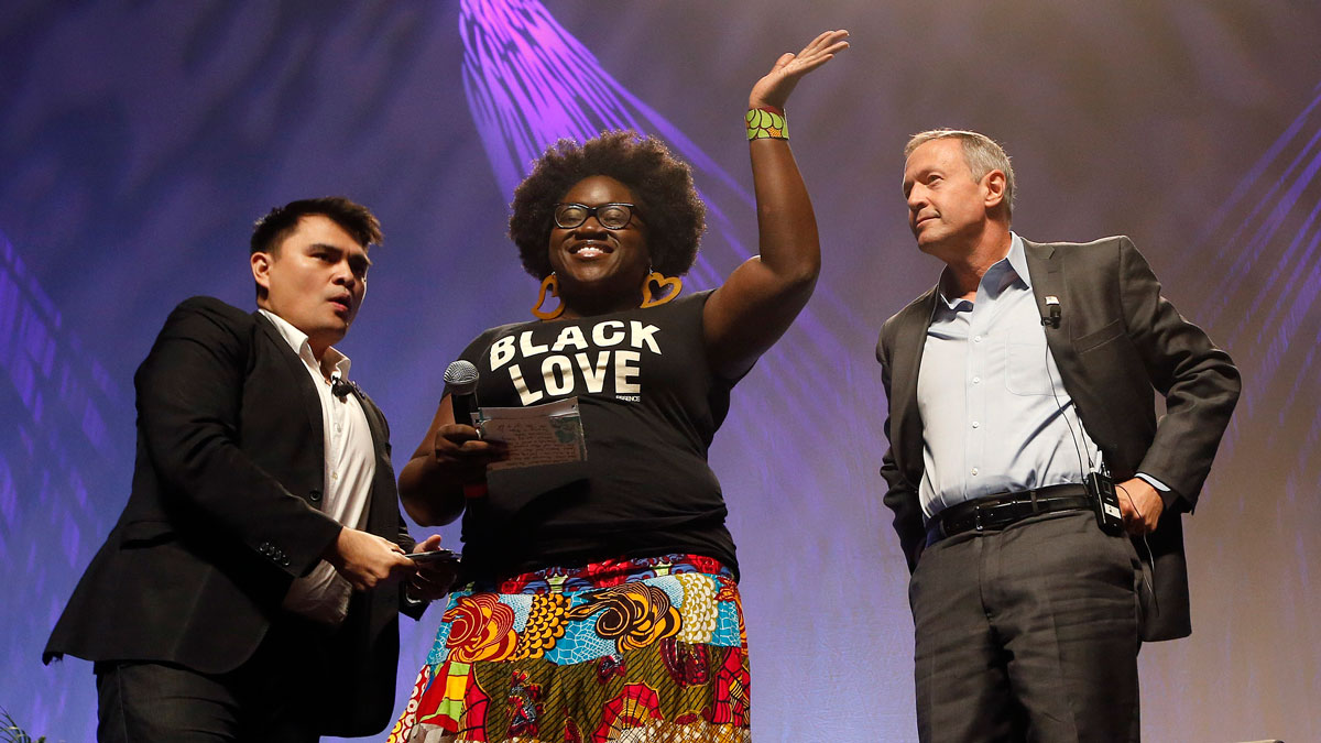 As dozens protesters shout, Tia Oso of the National Coordinator for Black Immigration Network, center, walks up on stage interrupting Democratic presidential candidate, former Maryland Gov. Martin O'Malley, right, as moderator Jose Vargas watches at left, during the Netroots Nation town hall meeting, Saturday, July 18, 2015, in Phoenix.