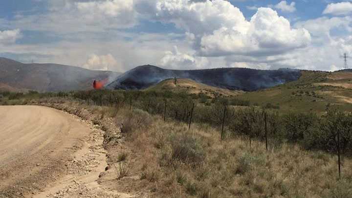 An aircraft drops water on a brush fire in Boise, Idaho, that authorities say was inadvertently set by a cyclist who tried to burn used toilet paper on Wednesday, July 22, 2015.