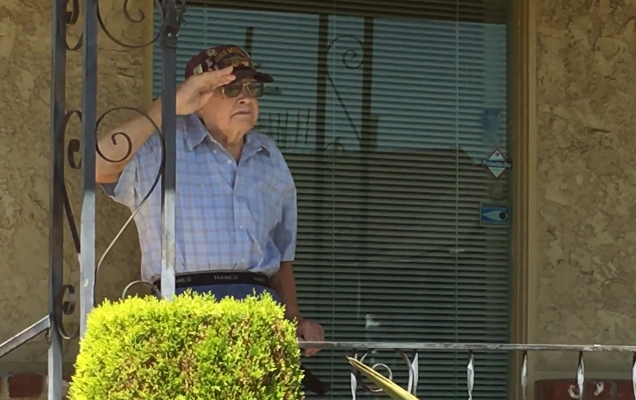 Veteran Ernest Thompson salutes members of the Navy Selects as they perform