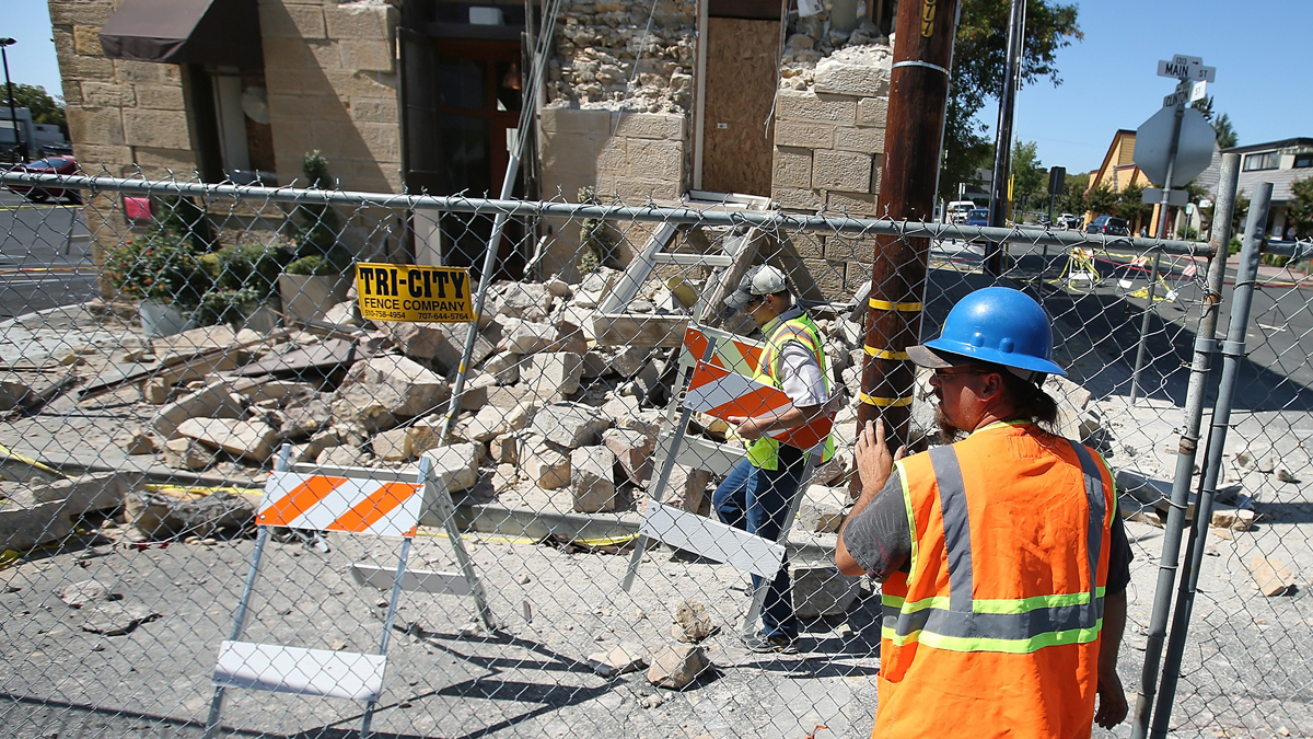 NAPA, CA - AUGUST 26:  Workers erect a fence around the earthquake-damaged Vintner's Collective building on August 26, 2014 in Napa, California.  Two days after a 6.0 earthquake rocked the Napa Valley, residents and wineries are continuing clean up operations.  (Photo by Justin Sullivan/Getty Images)