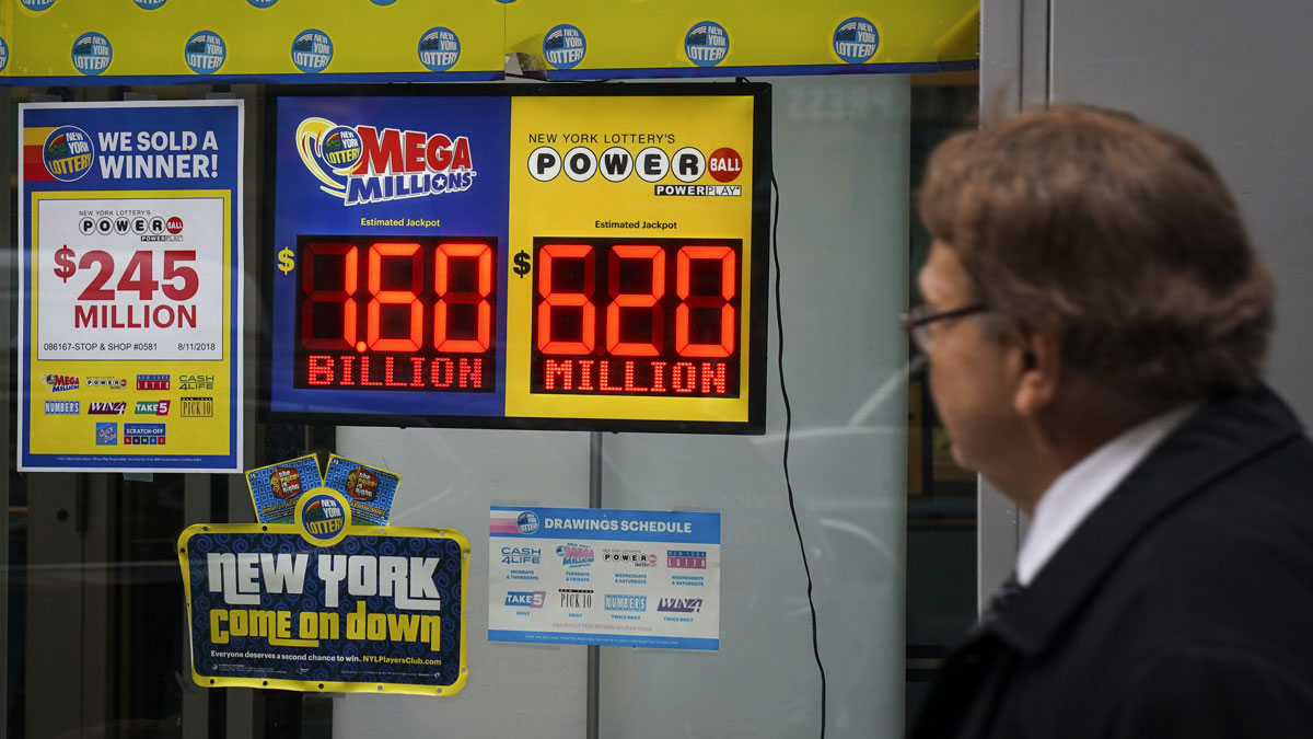 A man walks past advertisements for the Mega Millions and Powerball lotteries at the New York Lottery Customer Service Center in New York City on Tuesday, Oct. 23, 2018. The $1.6 billion Mega Millions prize drawn Tuesday night was the largest lottery prize in U.S. history.