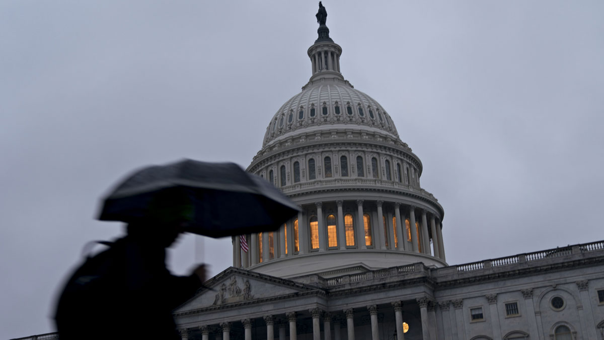 A pedestrian holding an umbrella walks past the U.S. Capitol in Washington, D.C., on Thursday, Dec. 20, 2018. President Donald Trump insisted on funding a wall or other barrier along the southern U.S. border as tensions over a possible partial government shutdown intensified in the wake of the presidents refusal to sign a stopgap spending bill.
