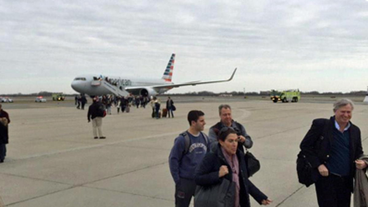 Passengers deplane from a remote area of JFK International Airport after authorities received a bomb threat by telephone.