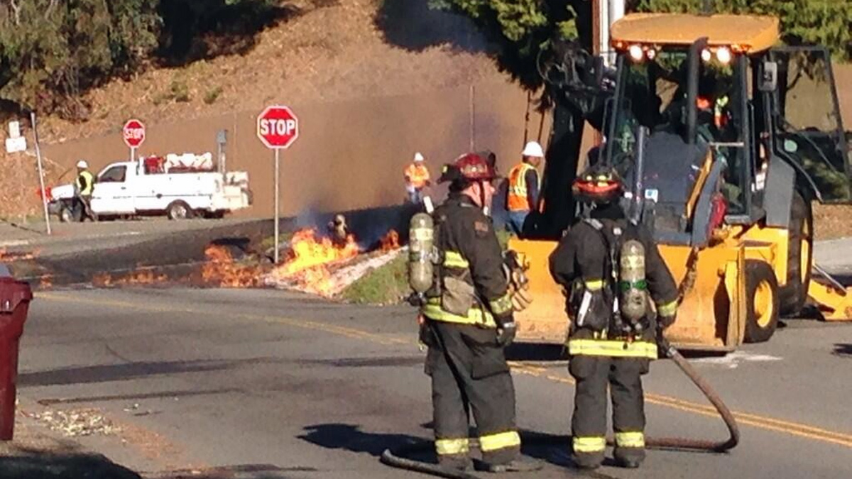 Firefighters began evacuating an Oakland neighborhood Tuesday morning after an underground gas line erupted into flames.