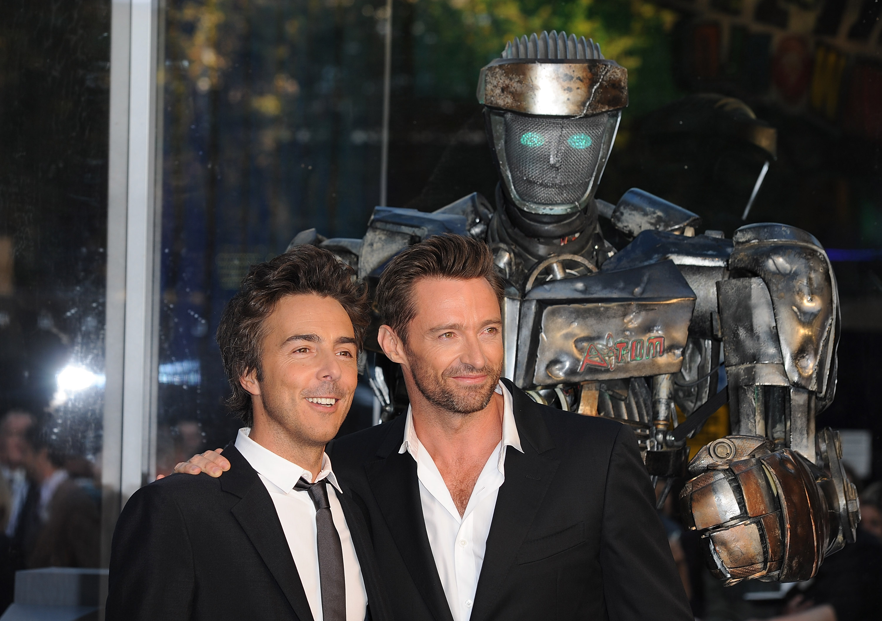 Director Shawn Levy (left) poses with Hugh Jackman and the robot boxer Atom from another film he directed,