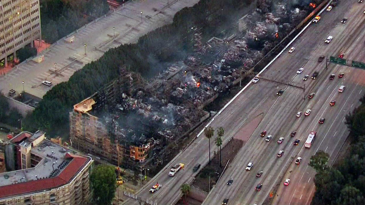 Traffic on the 110 Freeway moved slowly through the downtown LA more than 15 hours after a building under construction burned down on Monday, Dec. 8, 2014.