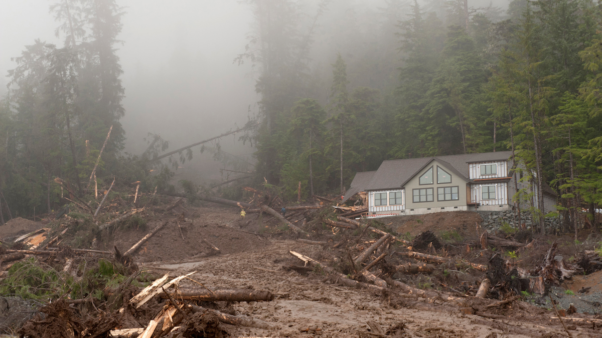 A house under construction is seen next to a landslide on Kramer Avenue, Tuesday, Aug. 18, 2015 in SItka, Alaska. Another house under construction, that was located to the left, was buried in the slide.  Four people working on it were missing Tuesday after heavy rain caused several landslides, emergency responders said.