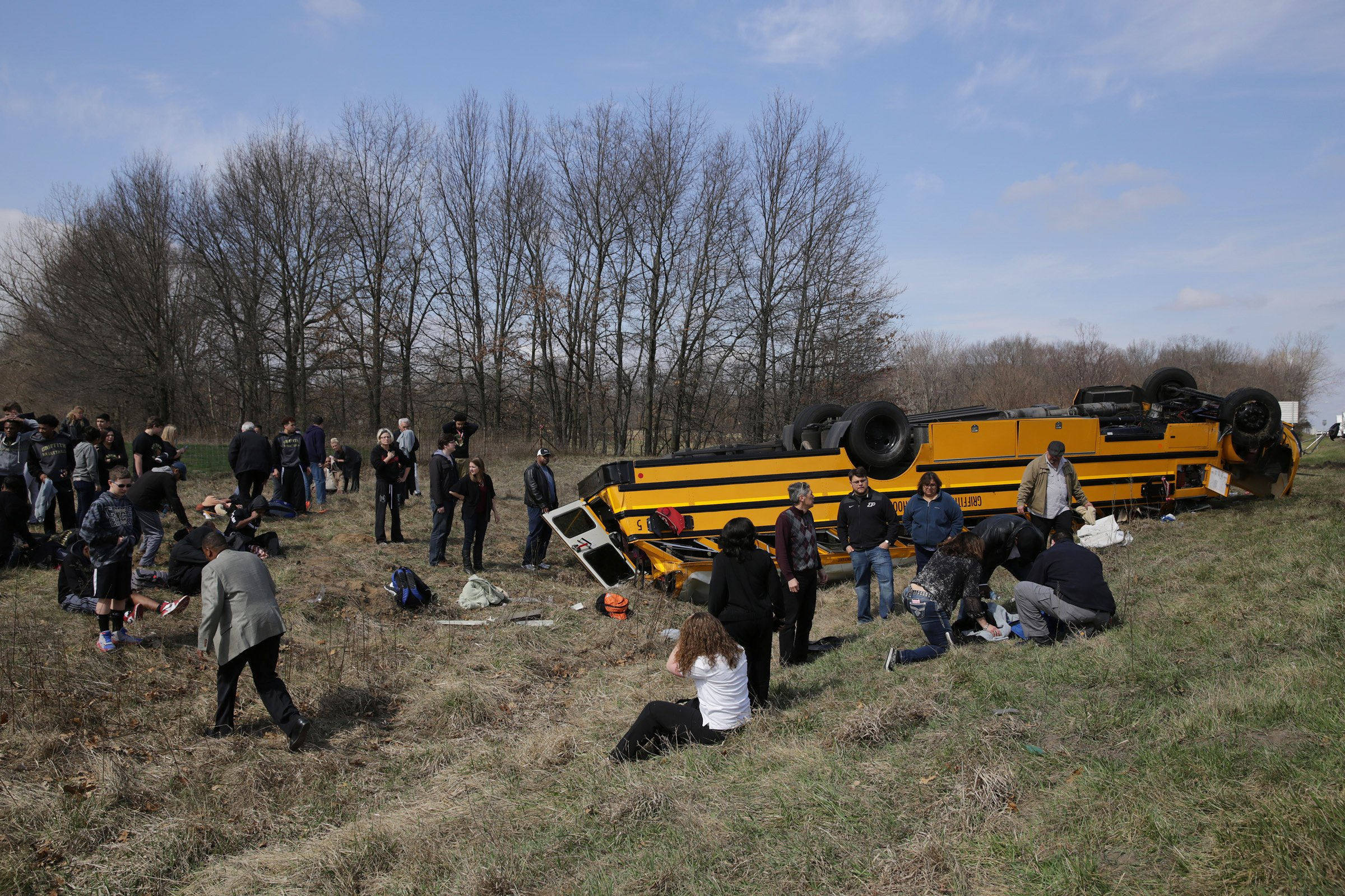 People on the scene of a school bus accident attend to the injured after the bus carrying Griffith High boys basketball team overturned in Demotte, Ind., Saturday, March 19, 2016. The bus rolled over on Interstate 65 on the way to Saturday's semifinal game against Marion at Lafayette Jefferson.