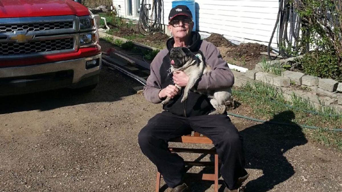 Hartley Bushell, 63, has decided to remain in Fort McMurray despite a raging wildfire that has devastated the Canadian city. Bushell is holding an abandoned pug that he found in a burned out neighborhood.