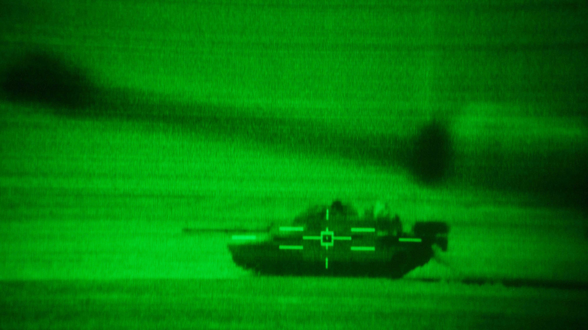 U.S. Army M1/A1 Abrams tank crews with 'Charlie' company 464 Armored Battalion are seen through the thermal imaging sights of a tank as they participate in task force maneuvers December 16, 2002, near the Iraqi border in the Kuwaiti desert. (Photo by Scott Nelson/Getty Images)