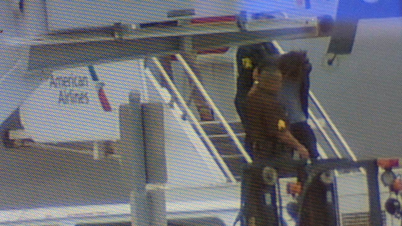 A man is led away in handcuffs by FBI agents after allegedly attempting to enter the cockpit on an American Airlines flight from Los Angeles to Honolulu on Friday, May 19, 2017.