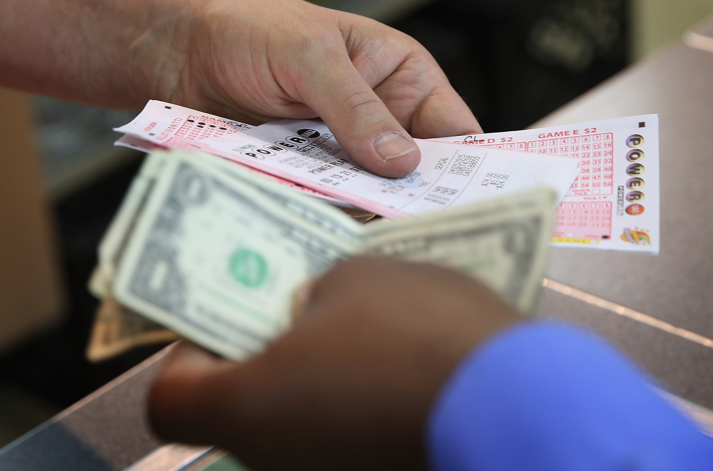 A customer purchases a Powerball lottery ticket at a 7-Eleven store on August 7, 2013 in Chicago, Illinois.